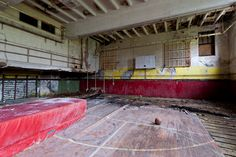A basketball, gym mat, and climbing ropes still remain in this heavily decayed elementary school gymnasium.