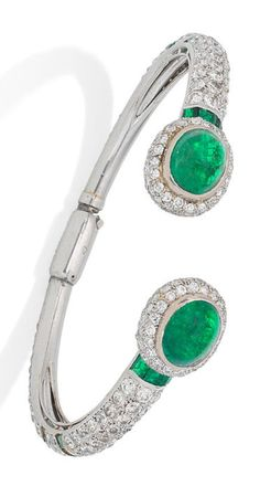 An Art Deco emerald and diamond torc bangle, circa 1930. The slender bangle entirely pavé-set with old brilliant and single-cut diamonds and calibré-cut emerald horizontal accents, each bombé terminal highlighted by a cabochon emerald, diamonds approximately 10.00 carats total, French assay mark.