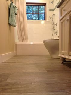 Magnificent Ceramic Tile That Looks Like Hardwood with White Tub Next to Bathroom and Planks