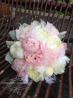 Blush pink peony and creamy ivory peonies make up a soft and romantic bridal bouquet with accents of white ostrich plumes and collared in dusty miller. Designed by Creative Weddings Floral Designs.