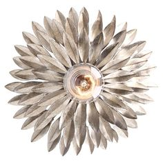 Cast a warm glow over your living room or foyer with this wrought iron wall sconce, showcasing a floral-inspired design and antique silver finish.