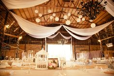 Perfect example of how to dress up a barn for a rustic wedding. Love the lights and streamers! #rusticwedding #barnweddings #weddingreception
