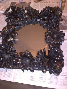 A pinner says: This is a mirror I made for one of my sisters for Christmas. I dipped fake flowers I plaster of paris and glued them on an unfinished frame. I spray painted it all black then dry brushed gold over the flowers. :-)