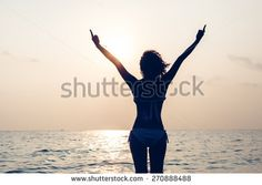 Free woman enjoying freedom feeling happy at beach at sunset. Beautiful serene relaxing woman in pure happiness and elated enjoyment with arms raised outstretched up. Latin Caucasian female model.