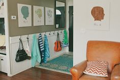 Hip- height board and batten with hooks in the entryway for kids to hang up their own stuff.