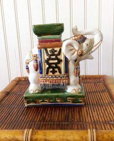 This is a sweet white ceremonial elephant, trunk up for good luck! Handpainted ceramic with colors of white, green, blue, caramel brown, black & plum. In very good vintage condition, no chips! Ready to prop up books on shelf, tabletop decor, mantle decor, or grouped with other collectables. Great for anyone who decorates with Chinoiserie or Asian Decor. Measures 6.75 height x 6.75 wide x 3 depth Thanks for shopping YellowHouseDecor!  Please visit my sisters shop for more vintage items ( e...