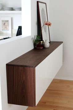 Create a faux credenza by mounting two Ikea Akurum kitchen cabinets next to each other on a wall. Surround the cabinets with stained wood to give a two-toned contrasting long wall credenza perfect for storing all your dining room essentials. For more information about how to make your own Akurum credenza visit Molly Madfis's blog Almost Makes Perfect.