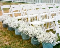 baby's breath in buckets. Cheap and adorable; would tie in well w/ baby's breath as the centerpieces.