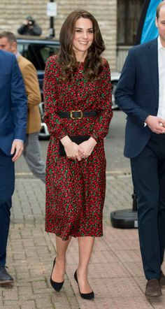 Duchess Kate wears a festive red-and-green printed Vanessa Seward dress with a simple black clutch and pumps.