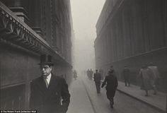 Light and shade: A sharply dressed man in a coat and top hat is clearly seen in the foreground, but an abundance of fog makes building disappear in the background