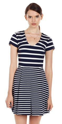 Our Chikara dress in nautical inspired mixed stripe print features a scoop neck, short sleeves, cinched waist and structured, pleated skirt.