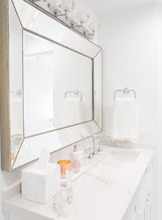 Silver frame mirror in white marble bathroom via Sydne Summer