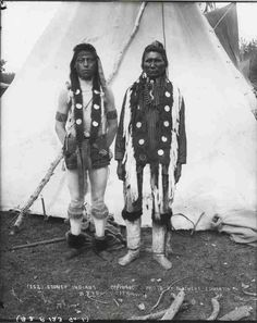 """""""Stoney Indians"""". Photo of two men standing outside of teepee. 1890s"""