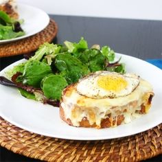 A decadent Croque Madame with gruyere and parmesan cheese  •8 tablespoons (1 stick) butter, divided   • 2 tablespoons flour   • 1 cup whole milk   • 1 bay leaf   • 1/2 teaspoon kosher salt   • 1/4 cup grated parmesan cheese   • 8 slices thick sourdough bread   • 8 to 12 slices good quality ham (about 3/4 pound)   • 12 ounces gruyere cheese, grated, divided   • 1 tablespoon vegetable oil   • 4 eggs   • freshly ground black pepper
