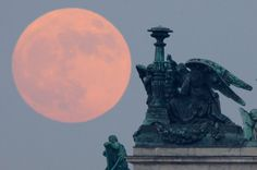 supermoon behind statues of angels fixed at the St. Isaak's Cathedral in St.Petersburg, Russia, Saturday, May 5, 2012