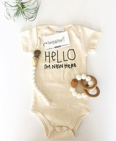 hello im new here hello world onesie onzie onsie layette bodysuit | newborn baby boy girl hospital coming home birth announcement outfit | gender neutral unisex baby clothes | wood silicone teething ring paci clip | organic cotton | baby flatlay