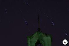 Filé d'étoiles derrière un clocher.