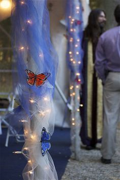 Column wrapped in tulle and white lights with feather butterfly decorations.