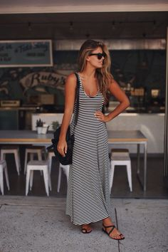 Beautiful long black and white stripped maxi dress. Paired with black sunglasses, black shoulder bag, and black strap sandals. Summer look on warm winter day? love her beach tossed hair