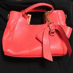 Coral handbag with bow detail Cute leather-like hand bag with bow detail on front. A detachable strap is also included. Bag has never been used. Divided compartment inside with a zipper center. Zipper pocket on outside. Also a small pocket inside for a cell phone and another zipper pocket on inside wall. Great coral color for spring and summer. None Bags Shoulder Bags