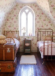 Romantic Vintage Bedroom... wooden floor, floral wall paper, old suitcase, cast iron beds
