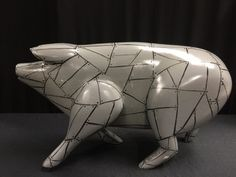 ONE OF A KIND HANDCRAFTED AND HAND-PAINTED TOM DOLAN SIGNED WOOD PIG. HE HAS A STEEL COLORED BODY WITH BLACK TRIM THAT GIVES HIM THE APPEARANCE OF HAVING RIVETED SHEETS OF METAL IN A STEAMPUNK FASHION. MEASURES 10 INCHES HIGH BY 17 INCHES LONG AND IS SIGNED ON THE BACK RIGHT LEG. SHOWS A BIT OF WEAR