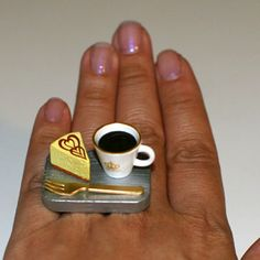 Dessert or Afternoon break.....A cup of coffee with a piece of Cheesecake and a fork for you to enjoy!!!   It measures approx. 1.35 inch wide and 0.75 inch high and is on a silver plated adjustable bang that will fit most ring sizes.