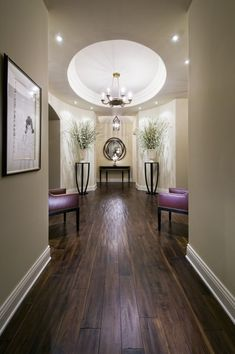New color direction - browns, creams with shot of great purple.  The chairs are excellent in style and color.  I love the symmetry in this hallway with the centered round in the ceiling.