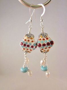 Absolutely gorgeous! This pair of earrings was created using gorgeous hand crafted bicone lampwork glass beads, accented with sterling