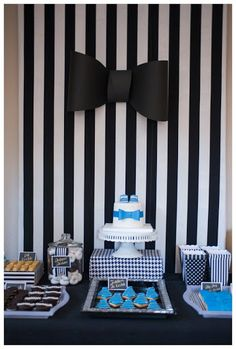 A dapper 1st first birthday boy party sweets, cookie and cake bar display. Pinstripes, bowties, ties patterns and tuxes. Black, white, blue and gold each dessert was loved by the kids. Popcorn, cakes, s