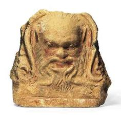AN ETRUSCAN TERRACOTTA ANTEFIX  CIRCA 4TH CENTURY B.C.  With the face of a satyr with pointed ears, balding pate and flowing beard and moustache, remains of arched attachment at back, traces of pigment