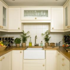 Small kitchen with cream cabinetry, wood worktops, butler sink and cream splashback tiles