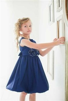 Your little girl will feel so pretty in this flattering Navy Blue bubble dress. She'll love how the taffeta fabric shimmers in the light. She'll also be surprised at how comfortable she feels; she'll be able to twirl in it all day! Beautifully hand crafted rosettes have been sewn on the waistline for an elegant look. Also available in Fuchsia, Red and Purple