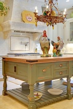 I love this aged green island and butcher block top, plus those big roosters and the chandelier.   The whole room is gorgeous