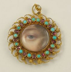 Eye Miniature Pendant - Ca 1830-1840 -   Magnificent miniature of a blue eye painted on ivory surrounded by brown curls and covered by a raised crystal. cannetille gold set with Persian turquoise and garnets with a pearl set in the pendant bail; compartment in the back is for hair, though empty; painting is incredible, much finer than most and very representative of Henry Bone.