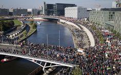 Angeblich eine Viertel-Million Menschen kamen beim TTIP-Protest in Berlin zusammen, um gemeinsam gegen die seit 2013 laufenden Verhandlungen des Freihandelabkommens zu demonstrieren. Die Menschenmassen mit Plakaten, Bannern und Schildern erstrecken sich bis zum Horizont.