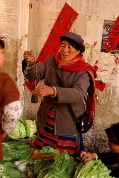 woman weighs cabbage in a Deqin market, Yunnan, China