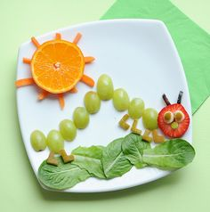 Very Hungry Caterpillar snack with grapes, strawberry, orange, pear, baby carrot, and baby spinach or lettuce