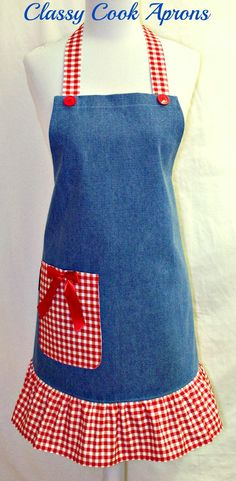 "A super cute apron in light blue medium weight denim, trimmed with a darling 5"" ruffle of red and white checked cotton, matching ties, plus a pair of big red buttons at bib corners. For a touch of panache, we added a nice big lined right hand pocket in red and white checks and christened it with a pretty red satin bow. And Ta-Da! Let's cook up something fun! $36.50"
