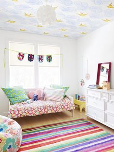 Daydream ceiling contrasted with a colorful rug and clean white walls - what a fun space (via HGTV Magazine)!