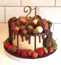 21st Birthday Chocolate drip cake. Layers of chocolate sponge with salted caramel buttercream. Covered with strawberries, forrero rocher, oreo, terry's chocolate orande and lindor
