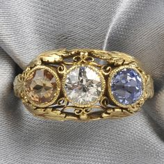 Arts & Crafts 18kt Gold Gem-set Ring, Edward Oakes, c. 1920-1930s, set with an old European-cut diamond weighing approx. 0.50 cts., a sapphire, and a topaz, the mount with foliate motifs and scrolling tendrils, size 4 1/2, unsigned.