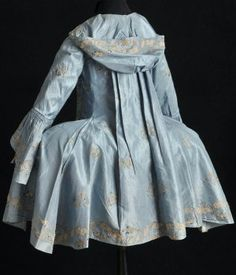 Caraco à la française, silk taffeta, embroidery, c. 1790, BM 27.738 Textil Museet, Borås, Sweden. [An unusual garment; I wish a front view was available. It has the hood, sacque back, and short length of the Brunswick, but seems to lack the lower sleeves and is definitely worn over paniers. The extremely late date is also unusual; Brunswicks, or German habits, were most popular in the middle part of the century.]