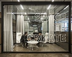 Glass encased meeting rooms are built into the interior design, acting as a place that supports not only tranquility and privacy, but also cooperation and clarity. capital letters illustrating the phrase 'space to create' is printed on the transparent surface, emblematic of the brand's trademark products: tools for mobile creation.