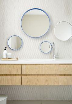 minimal color in the bathroom and the varying mirror heights are perfect for little ones