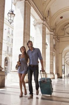 couple pulling suitcases