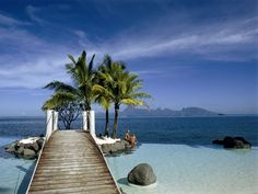 Tahiti: A dock juts out to a small palm island, surrounded by the jewel-blue waters of Tahiti.