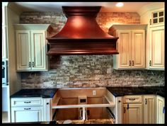 New copper hood and custom stone wall in kitchen in new construction home in Oldham County Kentucky by David Weis and Meridian Construction.