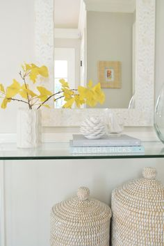 Faux ginkgo leaf in a sweater vase with a clear table in the foyer