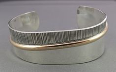 two_tone_sterling_and_14kt_gold_filled_wide_cuff_bracelet.  Love this cuff. It's simple, modern (without being cold), elegant, sleek and just beautiful.